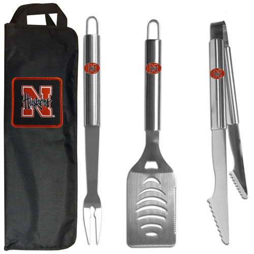 Nebraska BBQ Set w/Bag - Our Nebraska Cornhuskers stainless steel 3 pc BBQ tool set includes a large spatula with built in bottle opener, heavy duty tongs, and large fork. All the tools feature a team logo on the handle. The set comes with a durable canvas bag that has a chrome accented team logo.  Thank you for shopping with CrazedOutSports.com