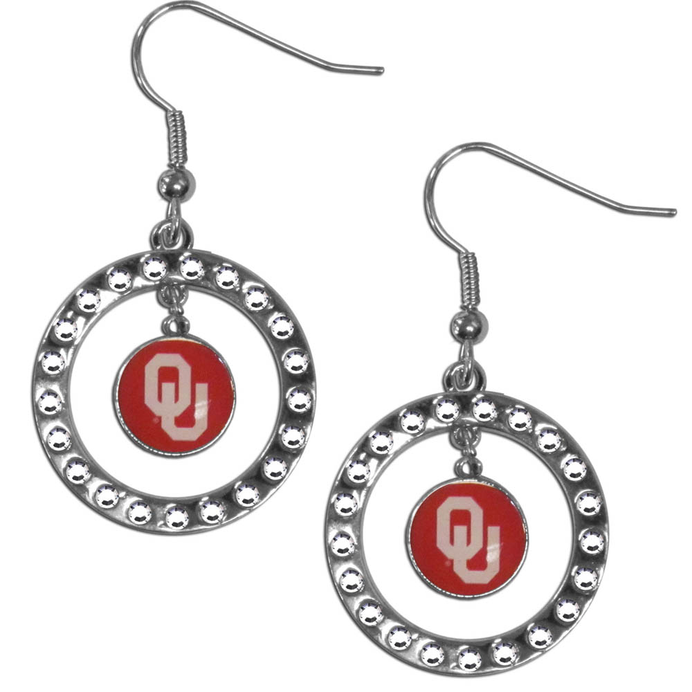 Oklahoma Sooners Rhinestone Hoop Earrings - Our officially licensed rhinestone hoop earrings comes on an hypo-allergenic fishhook posts  and features a hoop covered in rhinestones with a high polish chrome finish and a Oklahoma Sooners logo dangling in the center.