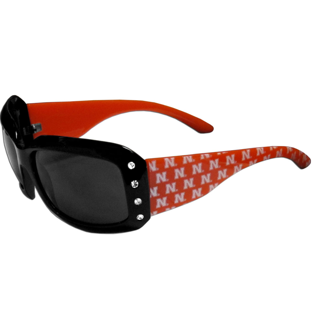 Nebraska Cornhuskers Designer Women's Sunglasses - Our designer women's sunglasses have a repeating Nebraska Cornhuskers logo design on the team colored arms and rhinestone accents. 100% UVA/UVB protection.