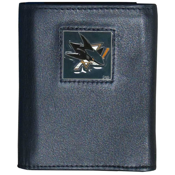San Jose Sharks® Leather Tri-fold Wallet - Our San Jose Sharks® leather tri-fold wallet features a sculpted and hand painted team square on a black leather tri-fold. Includes an ID window, slots for credit cards and clear plastic photo sleeves. For a sporty feel, the liner of the wallet is made with a canvas liner.