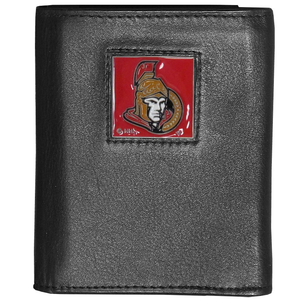 Ottawa Senators® Deluxe Leather Tri-fold Wallet - Our officially licensed fine grain leather wallet features numerous card slots, windowed ID slots, removable picture slots and large billfold pockets. This quality wallet has an enameled Ottawa Senators® emblem on the front of the wallet making it a stylish way to show off your team pride.