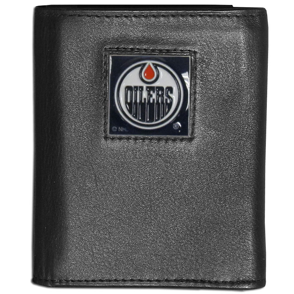 Edmonton Oilers® Leather Tri-fold Wallet - Our Edmonton Oilers® leather tri-fold wallet features a sculpted and hand painted team square on a black leather tri-fold. Includes an ID window, slots for credit cards and clear plastic photo sleeves. For a sporty feel, the liner of the wallet is made with a canvas liner.