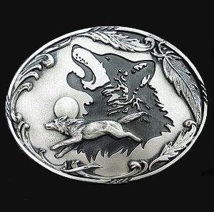 "Wolf Antiqued Belt Buckle - ""This belt buckle celebrates the wolf.  There is a wolf howling at the moon and wolf running surrounded by feathers and other design details.  This exquisitely carved buckle is made of fully cast metal with a standard bale that fits up to 2"""" belts.  Buckle is enhanced with diamond cuts and black enamel. """